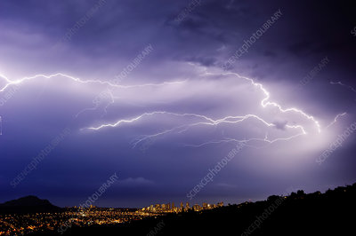 A lightning storm over a city in a valley