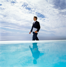 A man in a suit walking by a pool, carrying a laptop