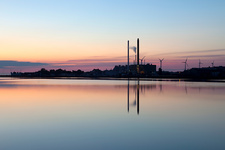 Smokestacks reflected in water