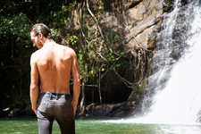 Bare chested man standing by waterfall
