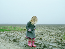 Girl wearing rubber boots on beach