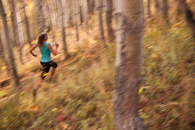 Blurred view of woman running in forest