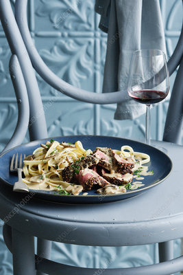 Bowl of beef stroganoff with wine