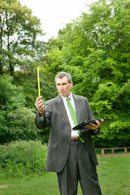 Businessman measuring distance in park