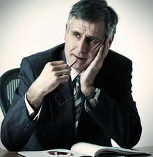 Businessman resting head in hand at desk