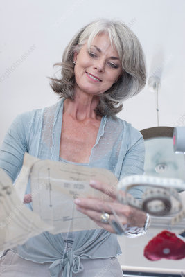 Older woman reading sewing patterns