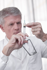 Doctor testing syringe in office