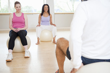 Women on exercise balls in gym class
