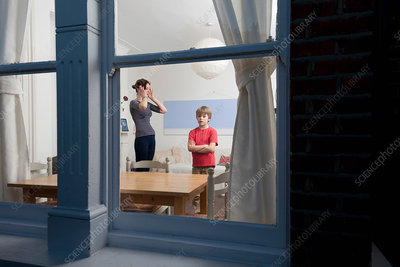 Mother and son viewed through window