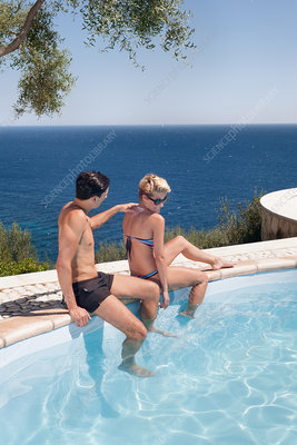Couple relaxing by outdoor pool