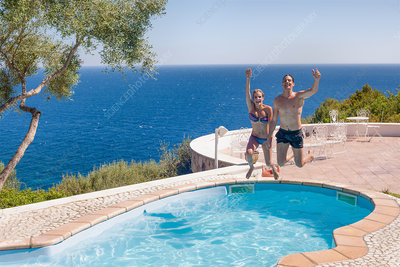 Couple jumping into swimming pool