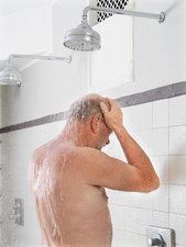 Older man showering in locker room