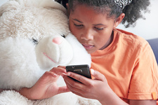 Girl using cell phone with teddy bear