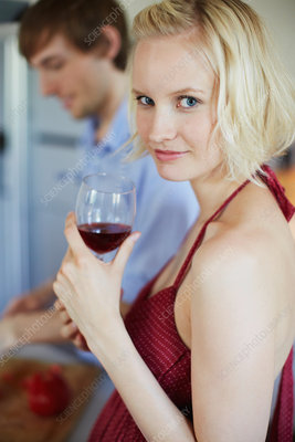 Smiling woman drinking wine in kitchen