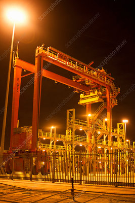 Cranes and ladders in shipyard at night