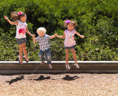 Children jumping together in park