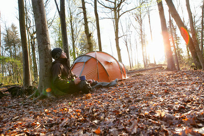 Man drinking coffee by tent in forest