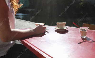 Woman having cup of coffee outdoors