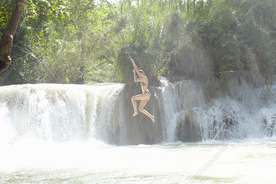 Woman jumping into rushing river