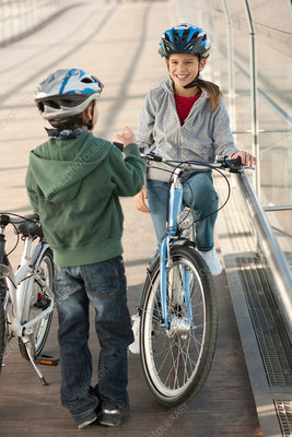 Children talking on bicycles in tunnel