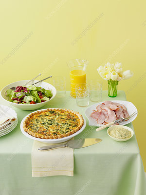 Table with quiche, ham and salad
