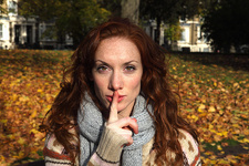 Woman holding finger over lips in park
