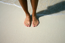 Close up of mans feet on beach