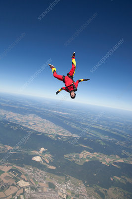 Woman skydiving over rural landscape