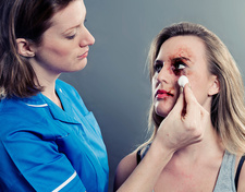 Nurse cleaning woman's bruised face