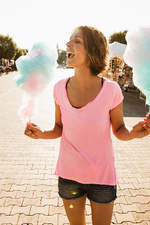 Woman eating cotton candy outdoors