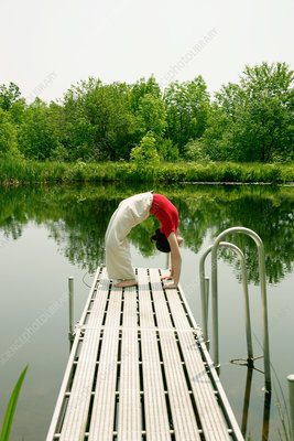 Woman practicing yoga on wooden pier