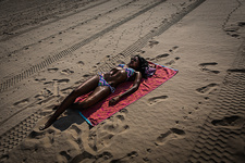 Woman sunbathing on towel on beach