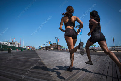 Women running together on wooden pier