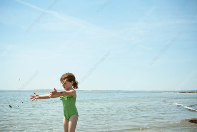 Girl playing with sand on beach