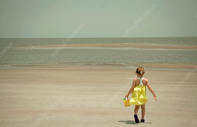 Girl carrying shovel and pail on beach