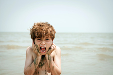 Boy playing with wet sand on beach