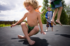 Boys jumping on trampoline outdoors