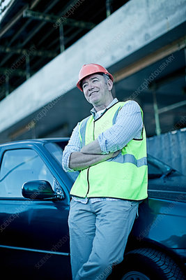 Construction worker leaning on car