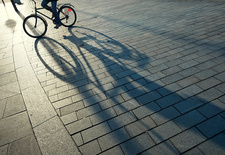 Bicycle casting shadow on city street