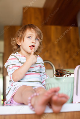 Girl tasting cake batter in kitchen