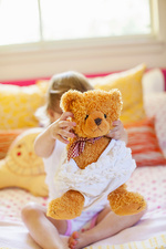 Girl playing with teddy bear on bed