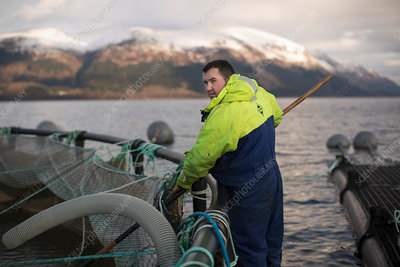 Worker at salmon farm in rural lake