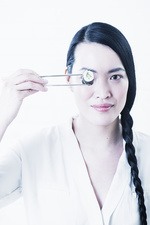Woman holding piece of sushi over eye
