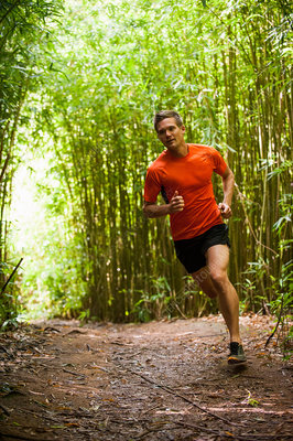 Man jogging on road in bamboo forest