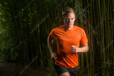 Man running on road in bamboo forest