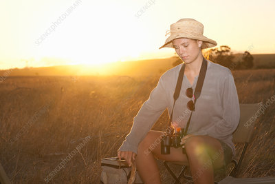 Young woman sitting on chair on safari, South Africa