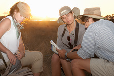 Three people looking at map on safari, South Africa