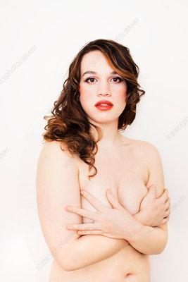 Nude young woman, covering breasts