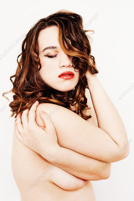 Nude young woman with hand in hair, eyes closed