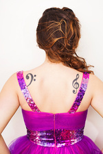 Rear view of a young woman with musical tattoos on back